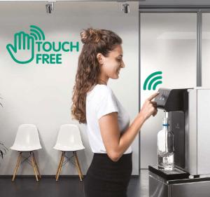 La fontaine à eau pour bureau et entreprise ecosoda sans contact. Efficace pour le zéro déchet et pour lutter contre le covid 19 (coronavirus). Une employée se sert une bouteille d'eau filtrée grâce au système à infrarouge (sans toucher le bouton).