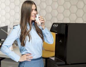 La fontaine à eau pour bureau et entreprise ecosoda black sans contact. Efficace pour le zéro déchet et pour lutter contre le covid 19 (coronavirus). Une dame boit de l'eau filtrée plate ou pétillante dans un verre.